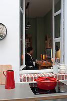 An original exterior window opens from the kitchen extension to the study, where Karine Clynkemaillie is working at her computer
