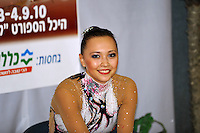 """Anna Alyabyeva of Kazakhstan smiles to camera at """"kiss & cry"""" during event finals at 2010 Holon Grand Prix at Holon, Israel on September 4, 2010.  (Photo by Tom Theobald)."""