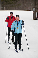 A senior couple cross-country ski at the Keweenaw Mountain Lodge in Copper Harbor Michigan in winter.