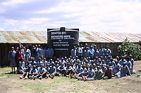 In Matanya, a small rural village near the base of Mount Kenya, students sit on the only auditorium they know - the bare earthen floor - where they pose with their new Rainwater Storage Tank, donated by Matanya's Hope.  This rainwater tank will serve the students, faculty and some visitors by providing a source of clean drinking water.  Without this tank, many of the students would be forced to collect their drinking and cooking water from a nearby muddy river which is laden with animal urine and feces.