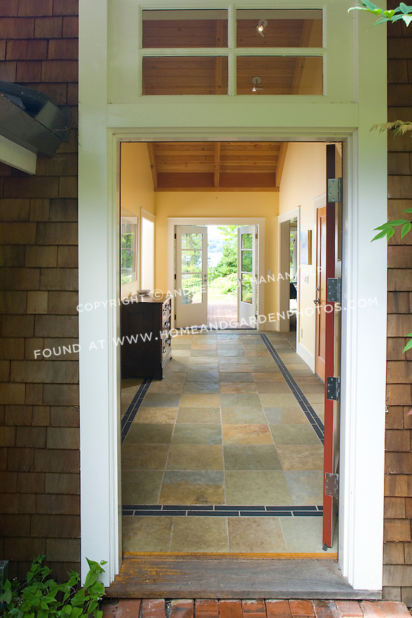 From the front porch, looking through the open front door and down a long, tiled, center hall to a pair of French doors leading to a brick patio, a sunny pocket garden, and views of the water at this waterfront weekend vacation retreat on Washington State's Vashon Island.