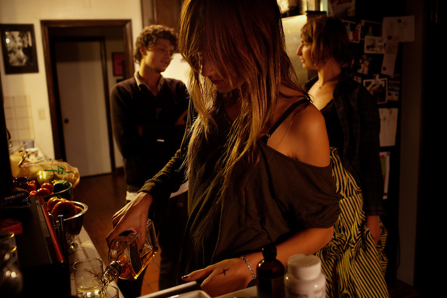 Los Angeles, California, August 1, 2009 - Moonrats guitarist, Nathan Thelen, left, talks with Warpaint guitarist Emily Kokal, while Warpaint guitarist/keyboardist, Theresa Wayman pours some whiskey in the kitchen of Thelen's home in the hills above Studio City. The two bands just finished a 10-day tour of the west coast. ..