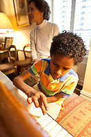Marilyn Berger (L), widow of Don Hewitt, sits next to Danny Hodes, the 8 year-old Ethiopian boy she has taken in, as he plays the piano in her apartment in New York, NY, USA, 9 April 2010. Ms Berger met him in Addis Ababa while reporting there and helped him get surgery.