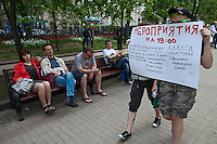 Moscow, Russia, 12/05/2012..Two women carry a poster for forthcoming events in Chistiye Prudy, or Clean Ponds, a park in central Moscow were some 200 opposition activists have set up camp.
