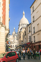 A busy street in Montmartre wth the basilique du Sacré-Coeur in the background