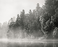 Sunrise on morning fog in native forest at Lake Matheson, Westland Tai Poutini National Park, UNESCO World Heritage Area, West Coast, New Zealand, NZ