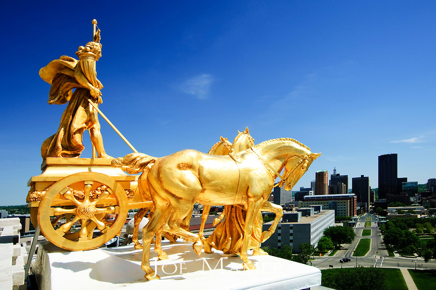 Quadriga located on top of the Minnesota state capitol in Saint Paul, Minnesota. The Quadriga represents the elements of nature.  The golden horses are held by two women who represent civilization, while the man on the chariot represents prosperity.