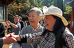 Asia, China, Yunnan, Kunming. Local Chinese temple visitors greet western tourists with a smile.