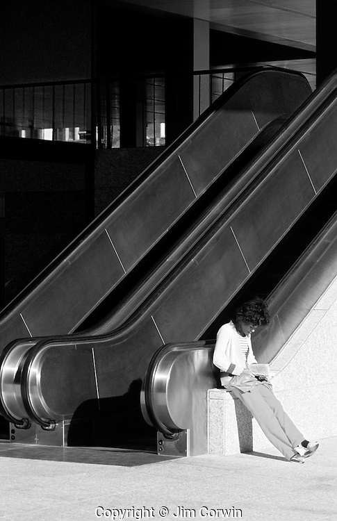 Woman reading book leaning against escalator downtown Seattle