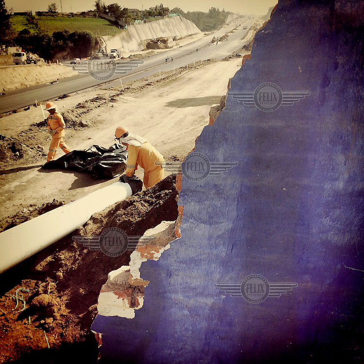 Workmen install water pipes beneath the newly constructed Ruta Viva (Living Road).