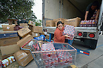 """Laura Rodriguez helps unload supplies at the Holding Institute in Laredo, Texas, on March 3, 2017. The clothing, food and other materials were donated by Cuban-Americans in other parts of the country and shipped by truck to Laredo for distribution to hundreds of Cuban immigrants stuck on the other side of the Mexican border, caught in limbo by the elimination in January of the infamous """"wet foot, dry foot"""" policy of the United States. They are not allowed to enter the U.S. yet most don't want to return to Cuba. Many churches in Nuevo Laredo, Mexico, have become temporary shelters for the immigrants, and congregations there rotate responsibility for feeding the Cubans. Such solidarity from ordinary Mexicans will be tested in coming months, as not only are the Cubans stuck at the border, but the U.S. has stepped up deportations of Mexican nationals, while at the same time detaining many undocumented workers from other nations and simply dumping them on the US-Mexico border. Rodriguez is a volunteer with Holding, an institution sponsored by United Methodist Women."""