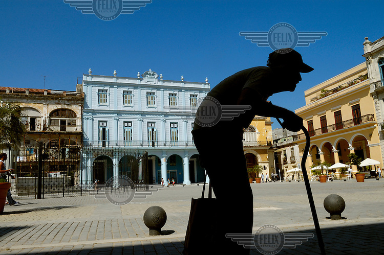 An elderly man (in silhouette) with a walking stick crosses the newly restored Plaza Vieja in Habana Vieja (Old Havana). Many of the renovated buildings in the city have been converted into hotels and restaurants catering for Western tourists.