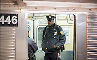 An NYPD officer riding a subway train stopped in Times Square in New York on Tuesday, March 22, 2016. Security in New York has been heightened in the wake of the terrorist bombings in Brussels, Belgium. (© Richard B. Levine)