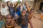 Children in Kano, Nigeria run toward the camera.