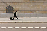 A pedestrian pulling a suitcase walks past the exterior of the British Embassy, the United Kingdom's diplomatic mission to Germany in Berlin. It is located on 70-71 Wilhelmstra&szlig;e, near the Hotel Adlon. Upon reunification in 1991, an architectural competition was won by Michael Wilford and the new building opened by Queen Elizabeth II on 18 July 2000.
