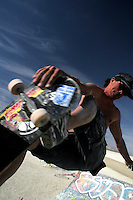 A young man rides his skateboard in Burning Man festival, Nevada, USA, September 3, 2005. .Born in Argentina, photographer Ivan Pisarenko in 2005  decided to ride his motorcycle across the American continent. While traveling Ivan is gathering an exceptional photographic document on the more diverse corners of the region. Archivolatino will publish several stories by this talented young photographer..Closer look at  Ivan's page www.americaendosruedas.com....
