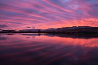 Spectacular pink sunrise reflection on Loch Ba, Rannoch Moor, Highland, Scotland