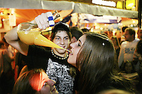 Switzerland. Canton Neuchâtel. Neuchâtel. Grape Harvest Festival. A young boy offers to a young girl a mixing of orange juice and strong alcohol drinks. Night life. © 2006 Didier Ruef ..