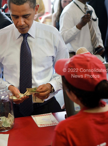 """Washington, DC - May 29, 2009 -- United States President Barack Obama pays for lunch at a """"Five Guys"""" burgers and fries restaurant Friday, May 29, 2009 in Washington, DC.  President Obama traveled with his motorcade to the burger restaurant in Southeast Washington.  .Credit: Brendan Smialowski - Pool via CNP"""