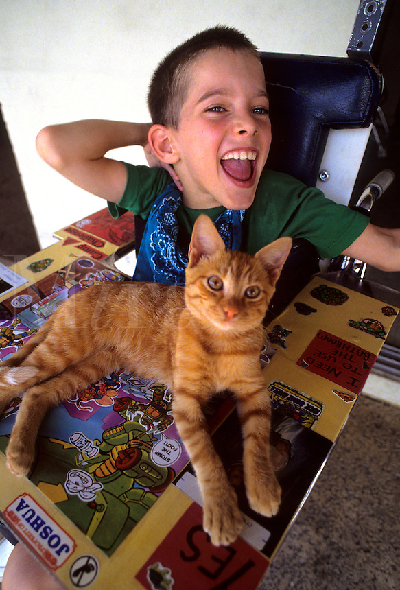 Handicapped boy in wheel chair with game and kitten with smile and good attitude.