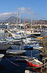 Assorted craft moored to the jetty in Los Cristianos harbour. Tenerife, Canary Islands.