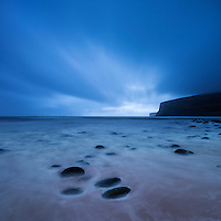 Clouds sweep across sky in fading light over beach at Rackwick Bay, Hoy, Orkney, Scotland