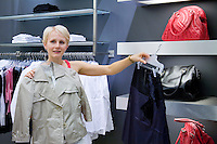 Woman looking and comparing different clothes in shop. Fashion, retail store, shopping. Shoulder bags on shelves.