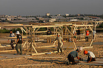 Settlers build wooden shacks at the Israeli outpost of Kerem Atzmona, in the Israeli settlement bloc of Gush Katif, in front of the Palestinian town of Khan Yunis, Gaza Strip.<br /> The compound is one of four, built in different settlements in Gaza, in order to accommodate the settlers' supporters from Israel and the West Bank, who are to assist resisting Israel's upcoming pullout from Gaza.