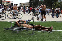 Mexico City, Mexico. 14th June 2014 - A man rests while people attend the 9th. Nudist Ciclotón 2014. With this protest demanding respect for vehicle users, to understand that the only thing protecting cyclists in the city is its clothing.. Photo by Miguel Pantaleon/VIEWpress