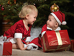 Eight month old baby boy doesn't want to share his Christmas gifts with a two year old girl