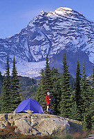 Woman setting up tent below Mount Rainier, Mount Rainier National Park, Washington