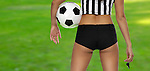 Sexy woman with a soccer ball and in referee outfit Isolated on green field background with clipping path and copyspace on the left