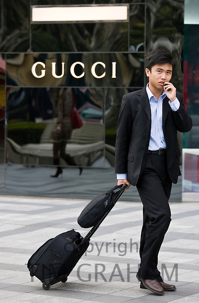Man with suitcase outside Gucci shop on Nanjing Road, central Shanghai, China