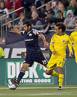 New England Revolution midfielder Monsef Zerka (19) dribbles as Columbus Crew defender Sebastian Miranda (21) defends. In a Major League Soccer (MLS) match, the Columbus Crew defeated the New England Revolution, 3-0, at Gillette Stadium on October 15, 2011.