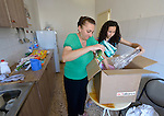 Lubna Nadar and her niece Sally Jahn unpack a box of household supplies in Amman, Jordan. The Christian women's two families, which fled from Mosul, Iraq after threats directed by the Islamic State, share a crowded apartment while they hopefully await repatriation to a third country. The families received a box of household supplies from International Orthodox Christian Charities, a member of the ACT Alliance.