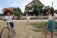 Kosovo. Village of Gaglavica. Young serbs boys and girls, wearing shorts and t-shirts. A kid holds a toy machine gun in his hand. War game. Bicycles. Kosovo (Albanian: Kosova) is a province of Serbia. While Serbia's sovereignty is recognised by the international community, in practice Serbian governance in the Kosovo province is virtually non-existent.  © 1995 Didier Ruef