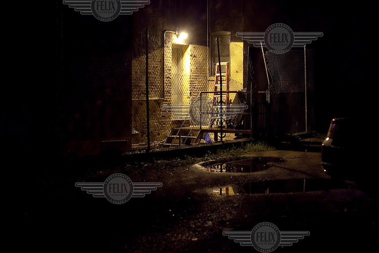 An alleyway, lit by a sodium lamp, in the East Village, New York.