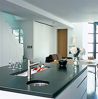 A broad kitchen island with a granite work surface dominates the centre of the kitchen with a dining area immediately beyond it