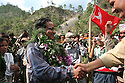 Prachanda (center) the supreme commander of the Maoist rebels, or People?s Liberation Army, is greeted as he arrives at a Maoist gathering in remote western Nepal on June 22, 2006. The ten-year old conflict in Nepal has claimed an estimated 13,000 lives. (Photo/Scott Dalton)