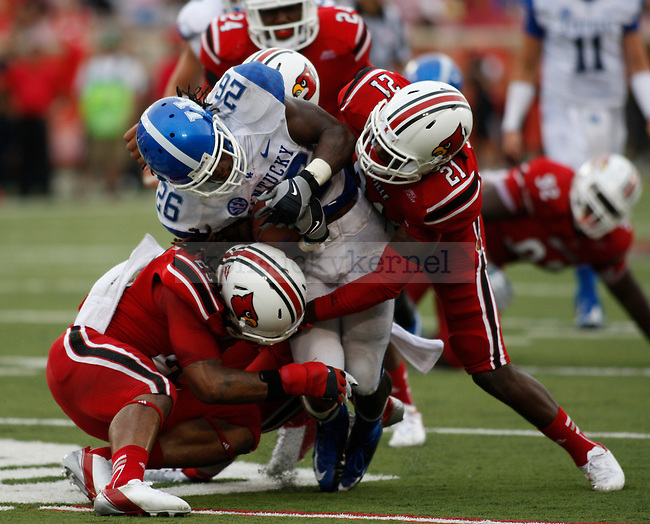 UK senior tailback CoShik Williams is tackled by UL players during the second half of the UK vs. UL football game at Papa John's Cardinal Stadium in Louisville, Ky., on Sunday, September 2, 2012. Photo by Tessa Lighty | Staff