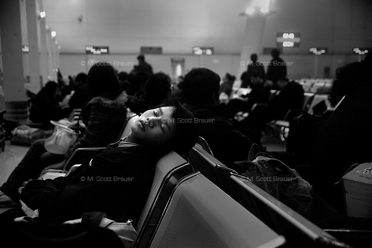 A train passenger sleeps in the Nanjing Railway Station in Nanjing, Jiangsu Province, China, while waiting for his train to depart late in the night.