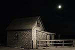 Full moon shines on moody coastal shanty.
