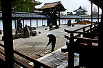 00559_05, Footsteps of Buddha, Kyoto, Japan, 2004, JAPAN-10003. A man rakes in a zen garden.<br />