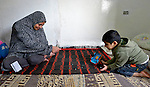 Souad Kasem Issa (left) is a Syrian refugee in Amman, Jordan. She and her husband and six children fled the city of Homs as fighting there worsened in 2012. Their home in Syria has since been destroyed by bombing, and they are struggling to survive in Jordan's capital city, where she plays marbles with her son Nour Eddin, 5. The family has received help from International Orthodox Christian Charities, a member of the ACT Alliance.
