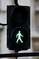 Green walk symbol on pedestrian crossing lights, London, United Kingdom