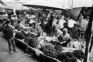 April 1970, Vientiane, Laos --- Street vendors sell bundles of marijuana, cigarettes, and tobacco in an open air market in Vientiane. --- Image by © JP Laffont