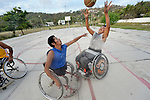 Manuel Rios shoots the basketball over Bartolome Martinez during practice in Zipolite, a town in Oaxaca, Mexico. Rios and Martinez play on the Oaxaca Costa wheelchair basketball team.