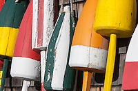 Close-up of colorful lobster trap buoys on the cedar shake covered wall of building in Maine.