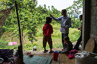 Ratna Baniya (28) talks to his eldest daughter Monika (7, in red) as their other relatives look on in their temporary home in Chautara, Sindhupalchowk, Nepal on 29 June 2015. The three girls lost their mother during the April 25th earthquake that completely levelled their house. Aastha was buried under the rubble together with her mother but Aastha survived. As their father Ratna Baniya (28) cannot care for the children on his own, SOS Childrens Villages has since been supporting the grandmother with financial and social support so that she can manage to raise the children comfortably and ensure that they will all be schooled. Photo by Suzanne Lee for SOS Children's Villages