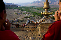 Two monks blow long horns on the roof of Thiksay Monastery, Leh, Ladakh, Jammu & Kashmir, India, on the morning of 1st June 2009. The horns are blown multiple times for 3 sets to announce the special morning prayers that will take place at 6am today. Special prayers like these happen about 4 times a year. Thiksay, founded in the 15th century, sits on a hill 19 km southeast of Leh town, and houses approximately 100 monks. Leh town can be seen in the background. Photo by Suzanne Lee